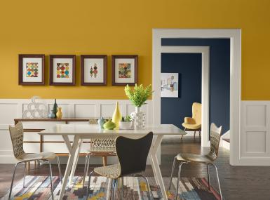 Golden yellow dining room with white accents looks through to navy walls of entryhall