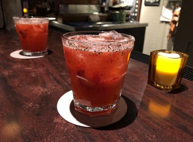 Wooden bar with two strawberry margaritas and a candle