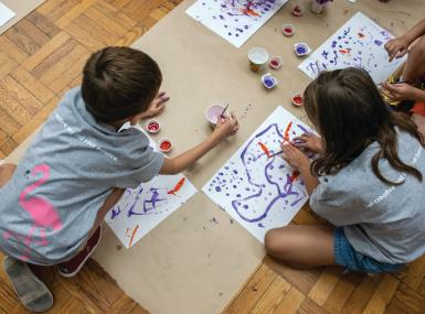 Children on floor sit in circle painting pictures