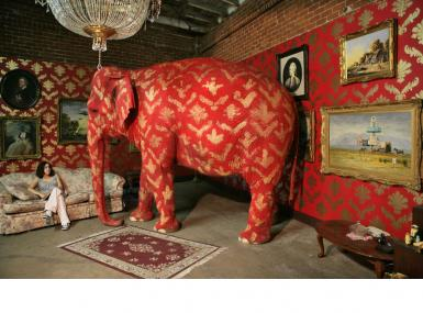 Staged room with woman on couch and live elephant painted red and gold to match wallpaper by banksy