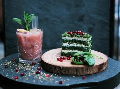 Pink cocktail and green and white layer cake with pomegranates sprinkled around wood board