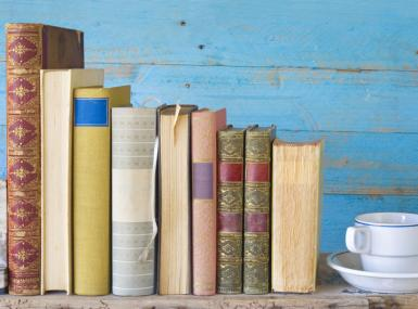 Antique books stand on table with coffee cup in front of rustic blue wall