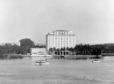 Black and white photo from Lake Worth of the old Whitehall Hotel with surrounding palm tree groves