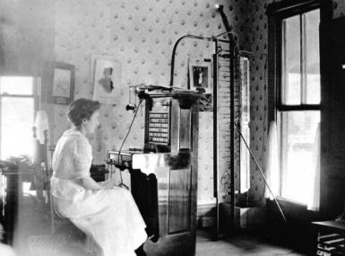 Black and white photo of woman in long white dress sitting at an early 1900's telephone switchboard
