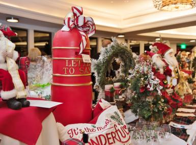 Silent auction table filled with Christmas wreaths and Santa decor