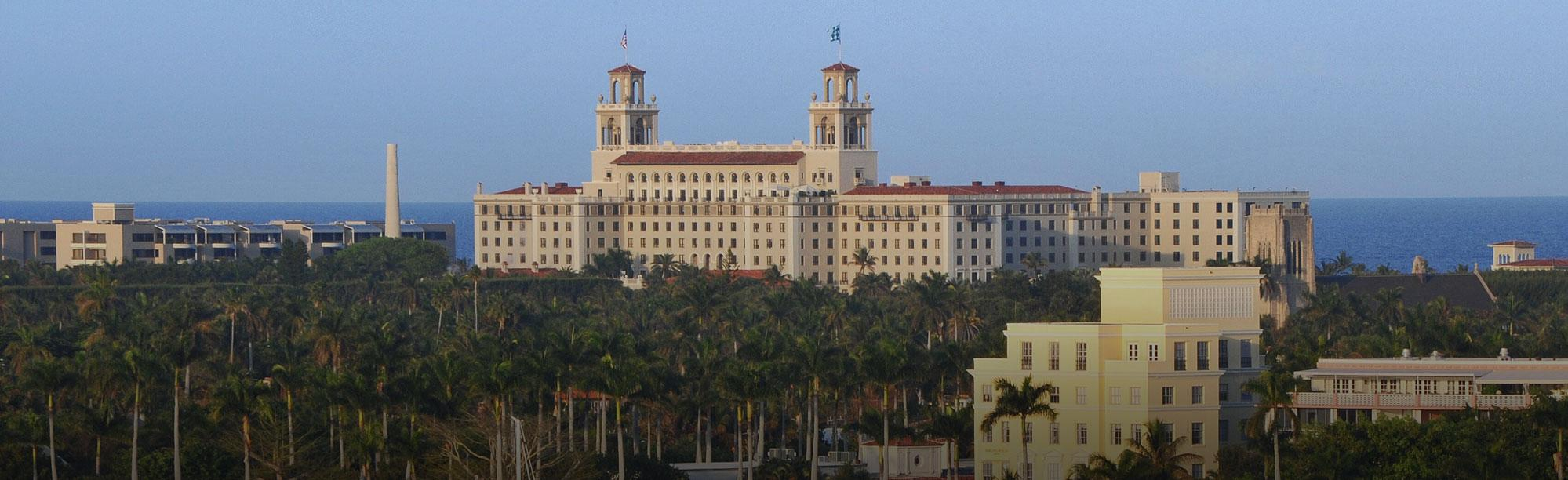 Breakers hotel stands tall in the background of a field of palm trees. The Ocean stretches in back.