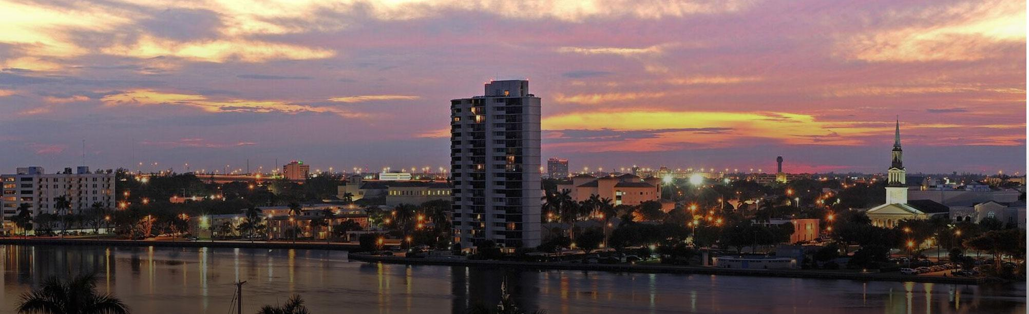 A yellow-orange sky at dusk. In this view of West Palm orbs of light litter the buildings.